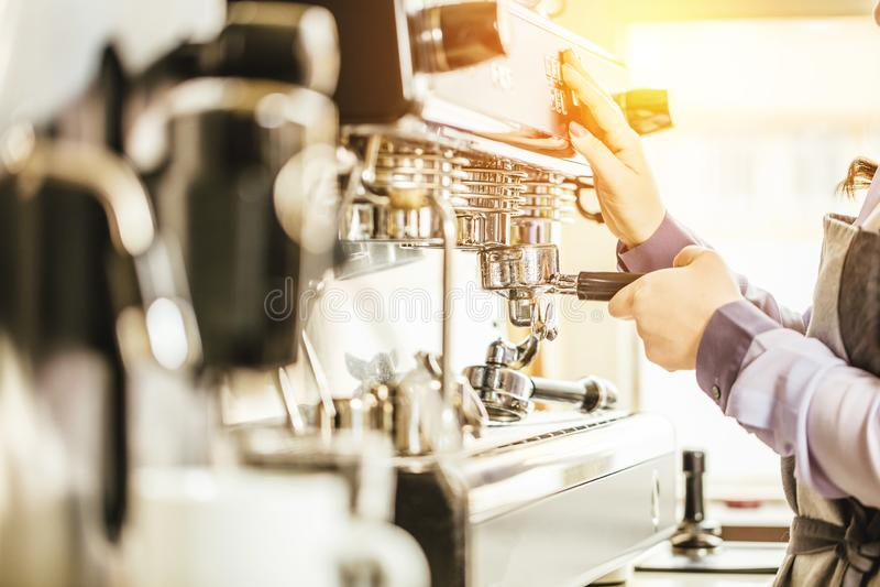Barista gebruikend koffiemachine om koffie in de koffie te maken stock foto