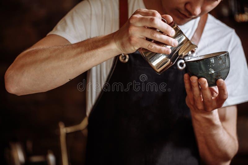 Barista giet melk in de drank stock fotografie