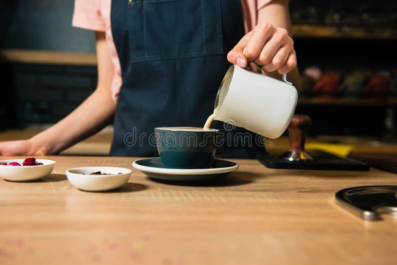 Barista giet melk van waterkruik uit stock fotografie