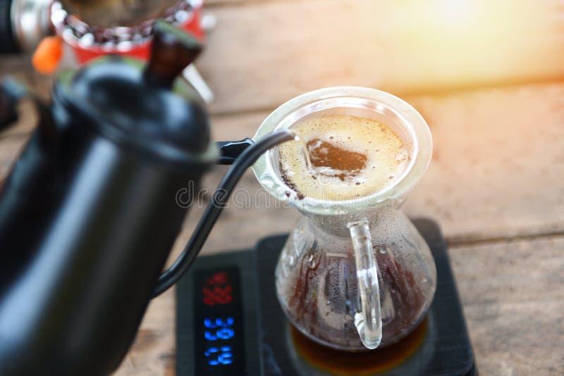 Barista gietend water van de druppelkoffie bij het gefiltreerde brouwen - maak kop druppelkoffie in glaskruik op het wegen schaal stock afbeelding