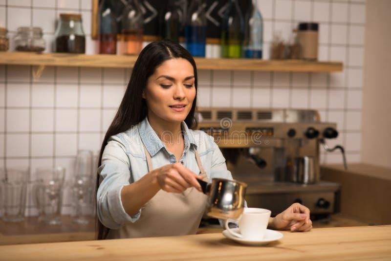 Barista gietende melk in koffie stock afbeeldingen