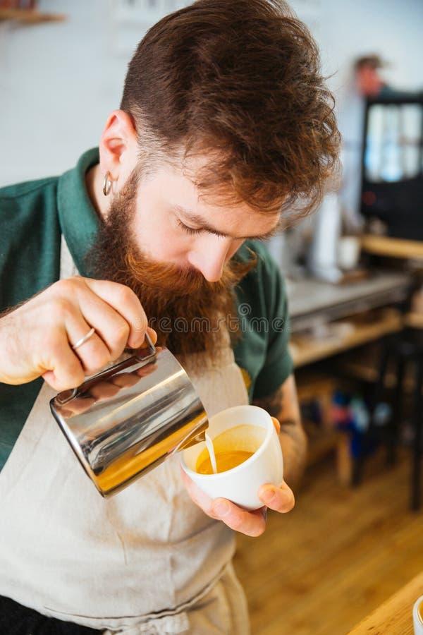 Barista gietende melk in kop van koffie stock foto's