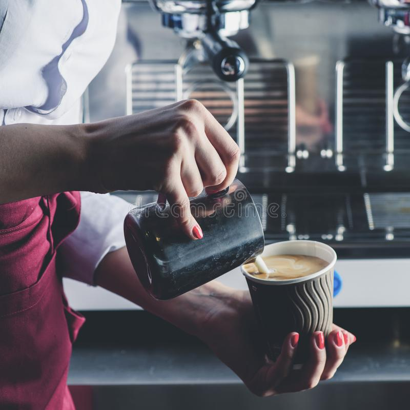 Barista girl pouring milk into coffee. Process of making cappuccino or latte royalty free stock photo