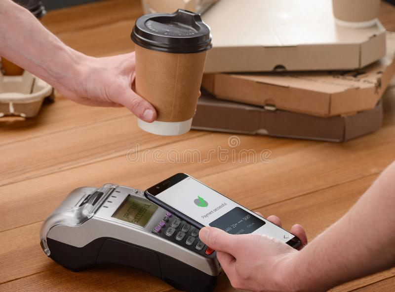 Barista giving a coffee cup. Barista giving a cup of coffee to the customer while he`s paying by phone stock photo