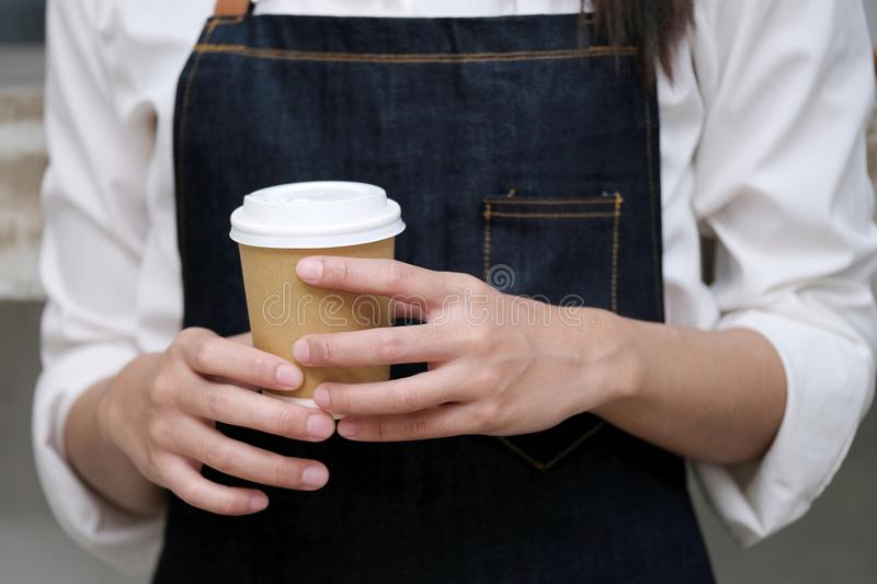 Barista hands holding a take away coffee cup with at cafe counter background, small business owner, food and drink industry royalty free stock image