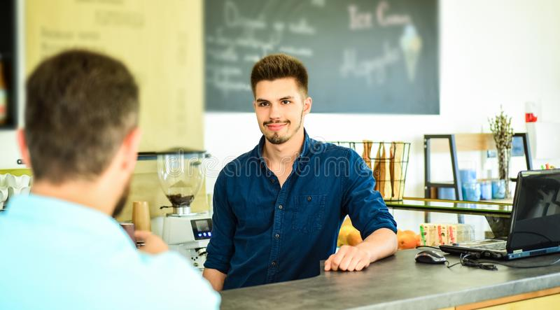 Barista handsome stylish hipster communicate with client visitor. Service staff qualification. Barista at bar of modern. Cafe ready to serve coffee for client royalty free stock photos