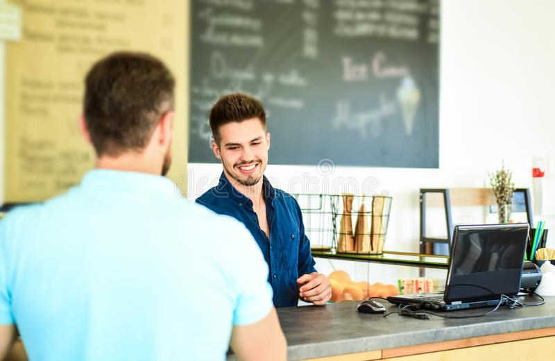 Barista handsome stylish hipster communicate with client visitor. Service staff qualification. Man ask for coffee at bar. Counter. Barista at bar of modern cafe royalty free stock photo