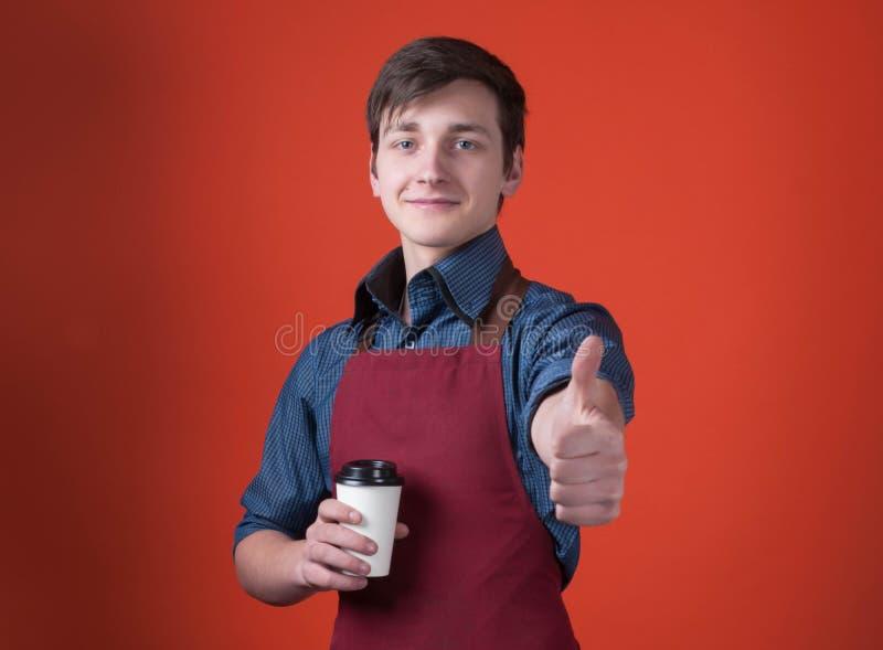 Barista hermoso con el pelo oscuro en el delantal de Borgoña que sostiene el café en taza de papel, mirando la cámara y manoseánd imagen de archivo