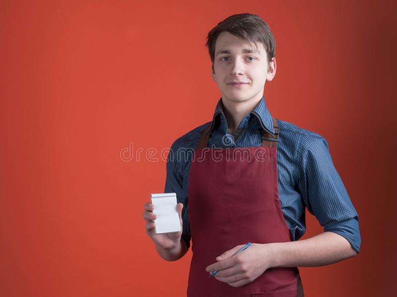 Barista holding notebook with copy space, pen and looking at camera royalty free stock photo