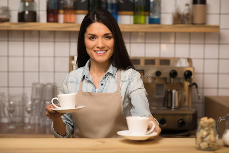 Barista holding two cups of coffee. Cheerful barista holding two cups of coffee and looking at the camera royalty free stock image