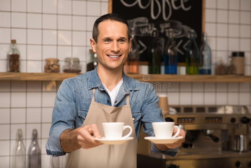 Barista holding two cups of coffee. Portrait of smiling barista holding two cups of coffee and looking away royalty free stock photo