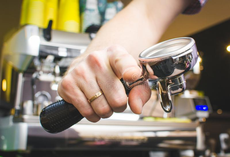 Barista holds a portafilter making coffee with a coffee machine. Toned picture royalty free stock photography