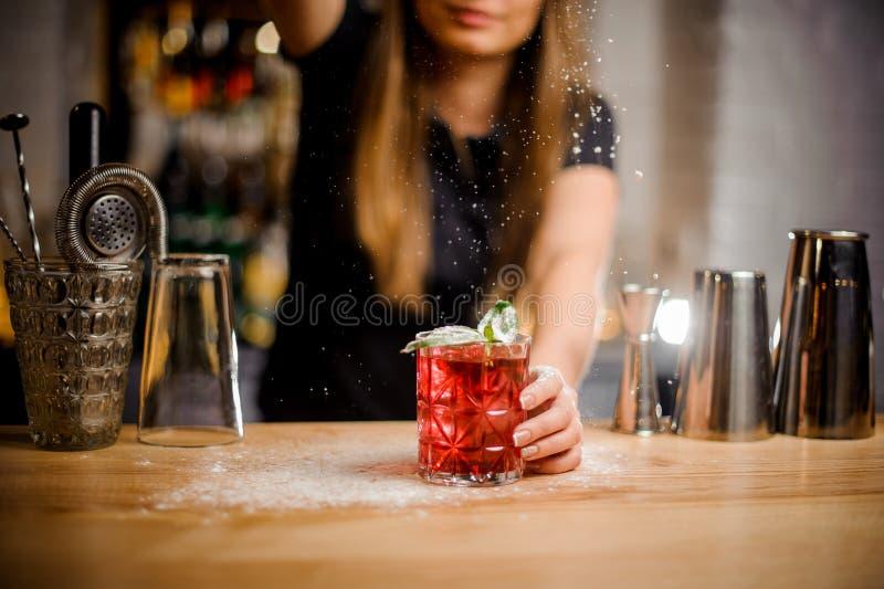 Barista kończy przygotowanie r koktajl z nowymi liśćmi dodawać gorzkiego sproszkowany cukier obraz royalty free