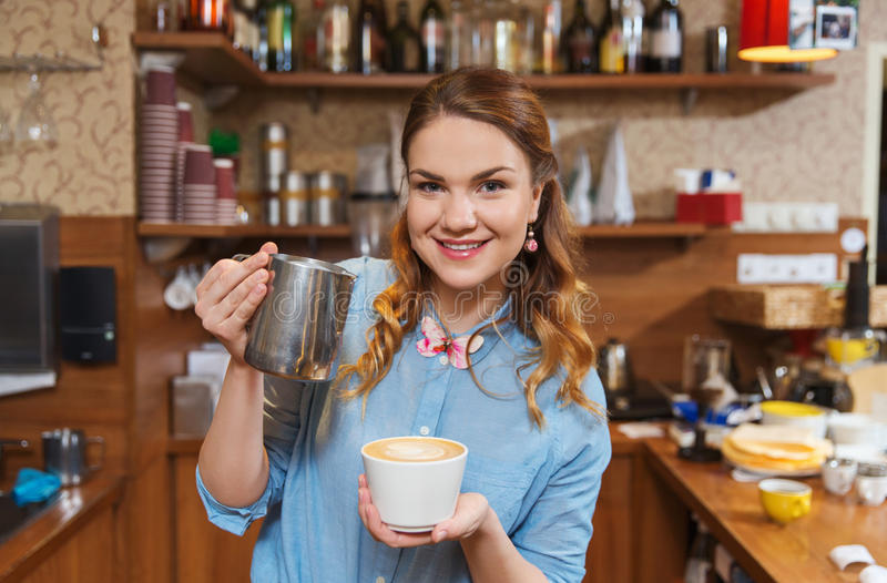 Barista kobiety dolewania śmietanka filiżanka przy sklep z kawą zdjęcia royalty free