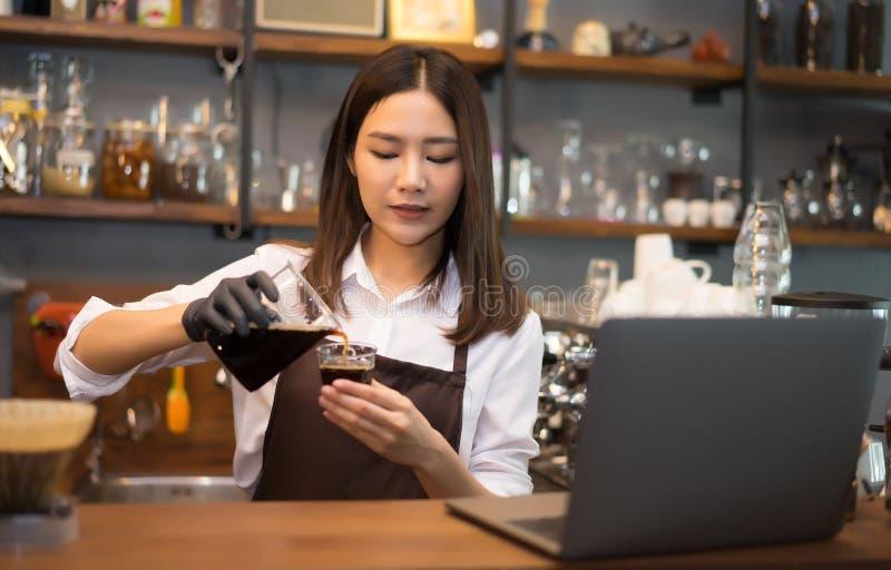Barista kobiety narządzania parzenia lodu kapinosa kawa za kontuarem zdjęcia royalty free