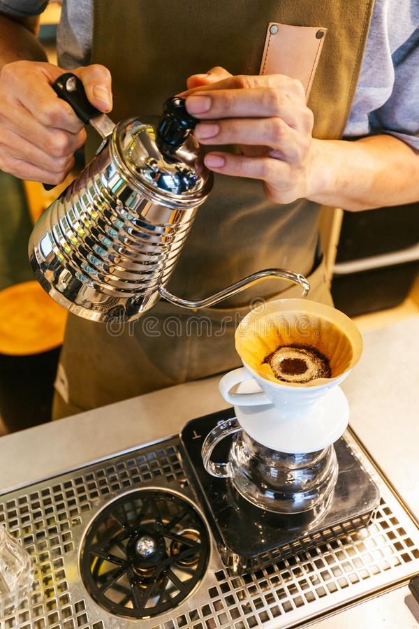 Barista maakt gipskoffie met de alternatieve methode Dripping Koffieslijpsel, koffiezetplaats en overvloeiing stock foto