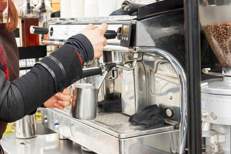 Barista makes coffee in coffee machine royalty free stock images