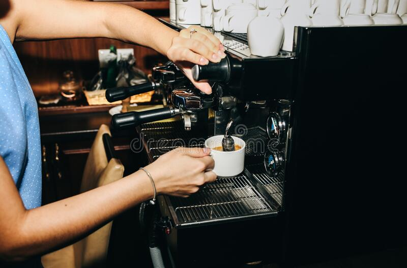 Barista is making black coffee americano. Girl is holding a white cup in her hands near the professional coffee machine. Food and royalty free stock images