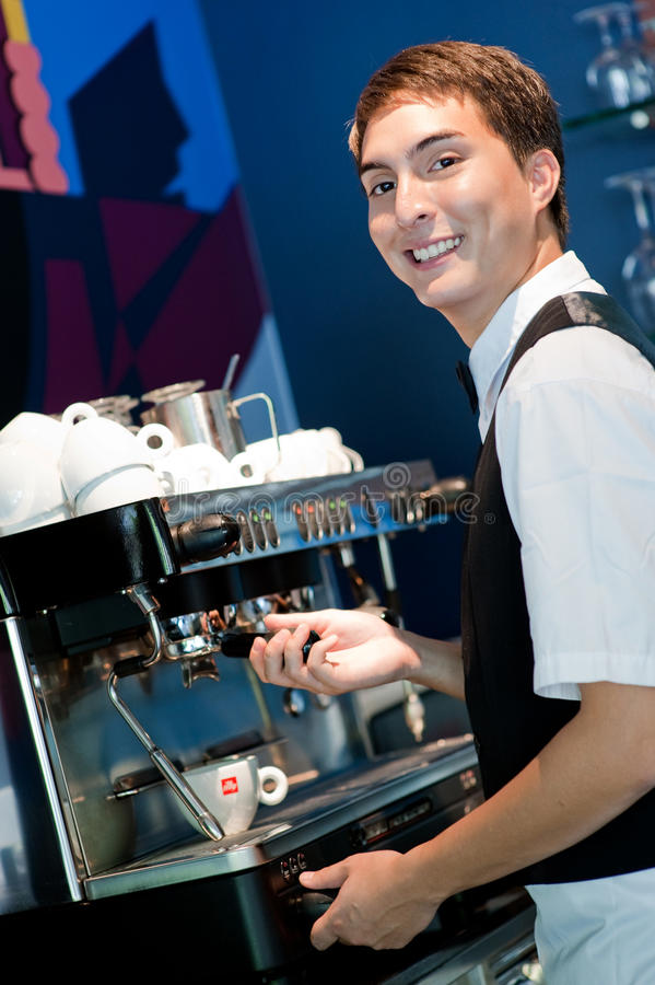 Barista Making Coffee. A young and attractive barista making a coffee in an indoor restaurant stock photo
