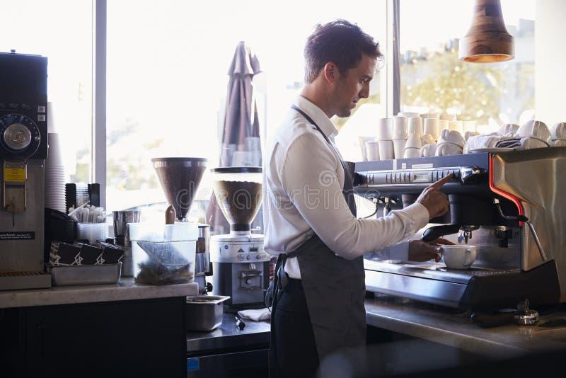 Barista Making Coffee In matvaruaffär genom att använda maskinen arkivfoton
