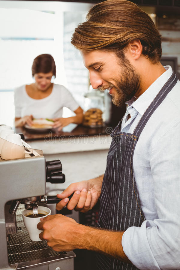 Barista making a cup of coffee royalty free stock image