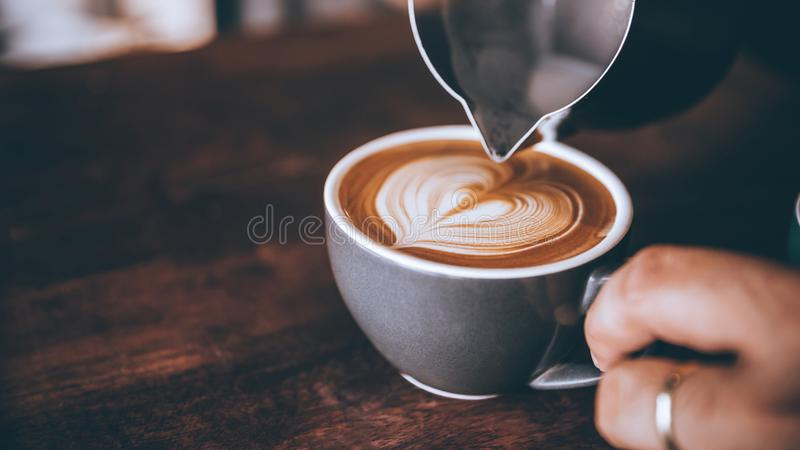 Barista making pouring stream milk with coffee latte art pattern heart shape stock photography