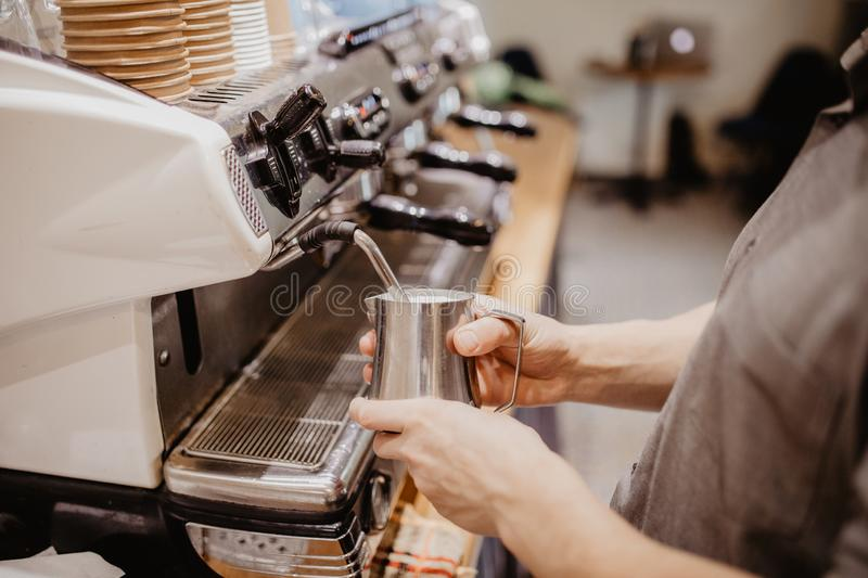 Barista man hands steaming milk for hot cappuccino with machine at the coffee shop in morning royalty free stock photos