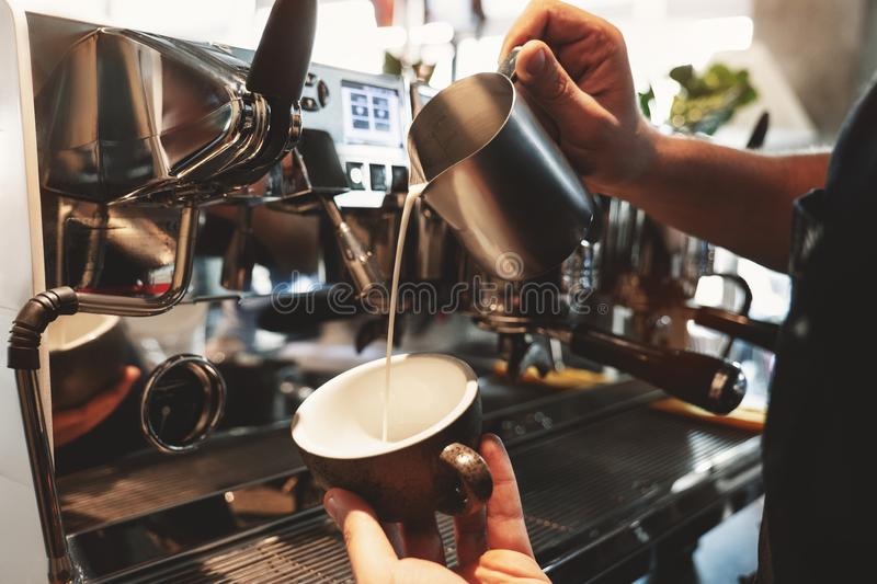 Barista man pouring whipped milk from frothing pitcher in cup with coffee standing near professional coffee machine in. Cafe royalty free stock image
