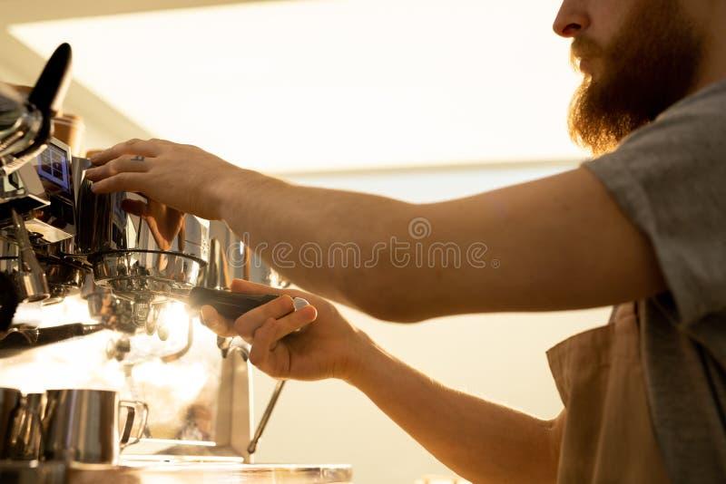 Barista man som fäster portafilter till espressomaskinen arkivbild