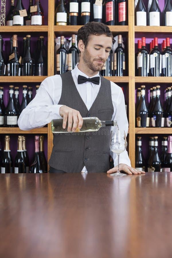 Barista maschio Pouring White Wine in vetro fotografia stock