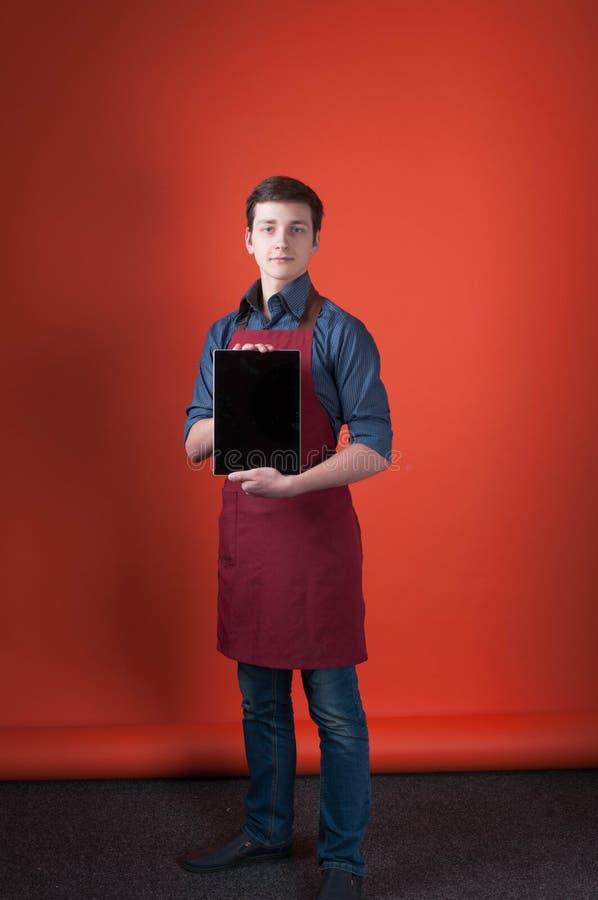 Barista met donker haar in de blauwe overhemd, jeans en schort die van Bourgondië digitale tablet houden stock afbeelding