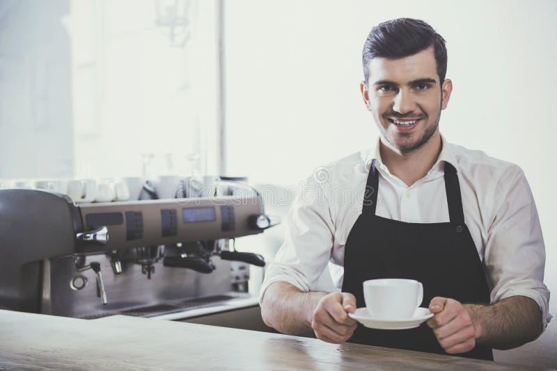 Barista met kop van koffie in zijn handen royalty-vrije stock afbeelding