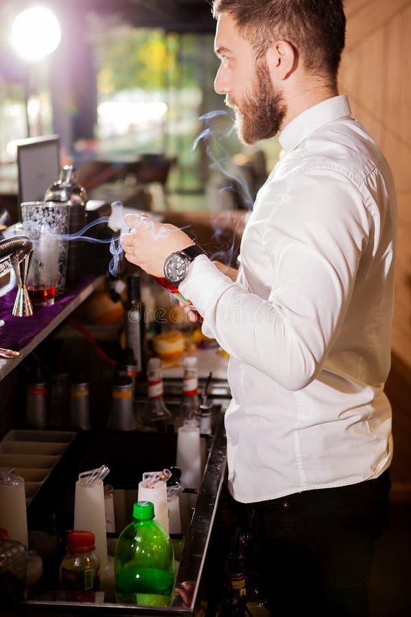 Barista nella bevanda di versamento della camicia bianca incredient fotografia stock