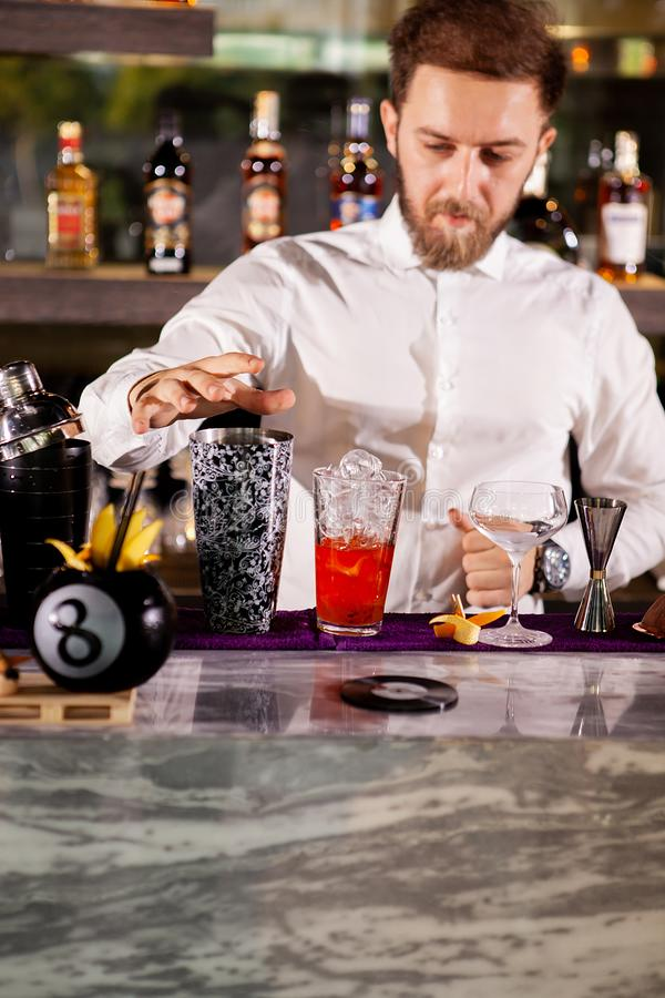 Barista nella bevanda di versamento della camicia bianca incredient fotografie stock