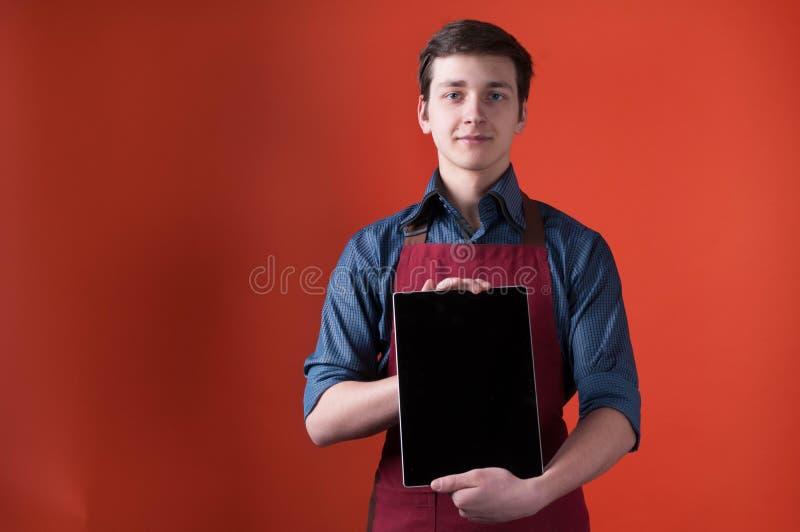 barista no avental vermelho que olha a câmera e que mostra a tabuleta digital com a tela vazia perto do fundo coral da cor fotos de stock