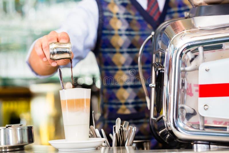 Barista no café de derramamento do café disparou no macchiato do latte fotografia de stock royalty free