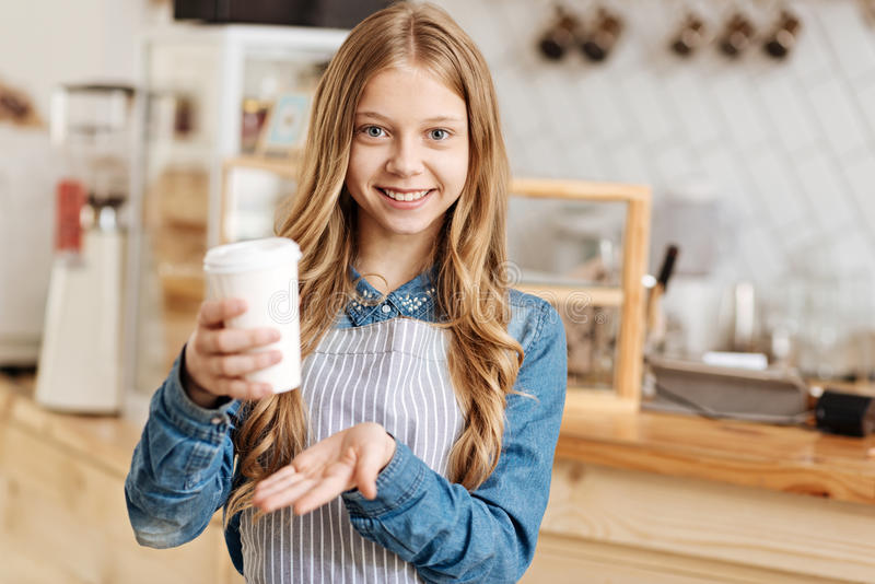 Barista novo alegre que guarda uma xícara de café fotografia de stock