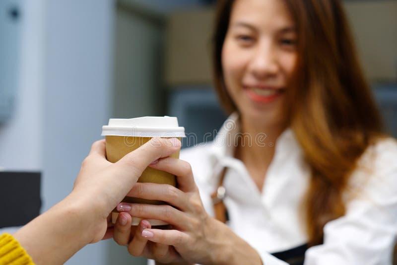 Barista novo da mulher de Ásia que serve um copo de café diaposable com manutenção programada fotografia de stock