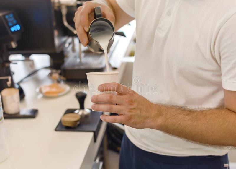 Barista novo que derrama e que serve para ir forrar a x?cara de caf? fotografia de stock royalty free