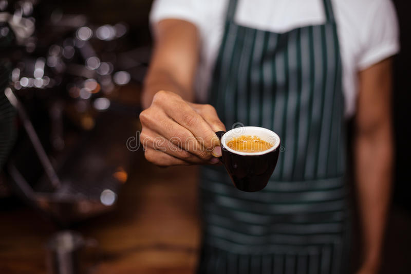 Barista offering an espresso. In the coffee shop stock images