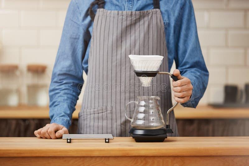 Barista på stångräknaren omkring som gör pouroverkaffe royaltyfri foto