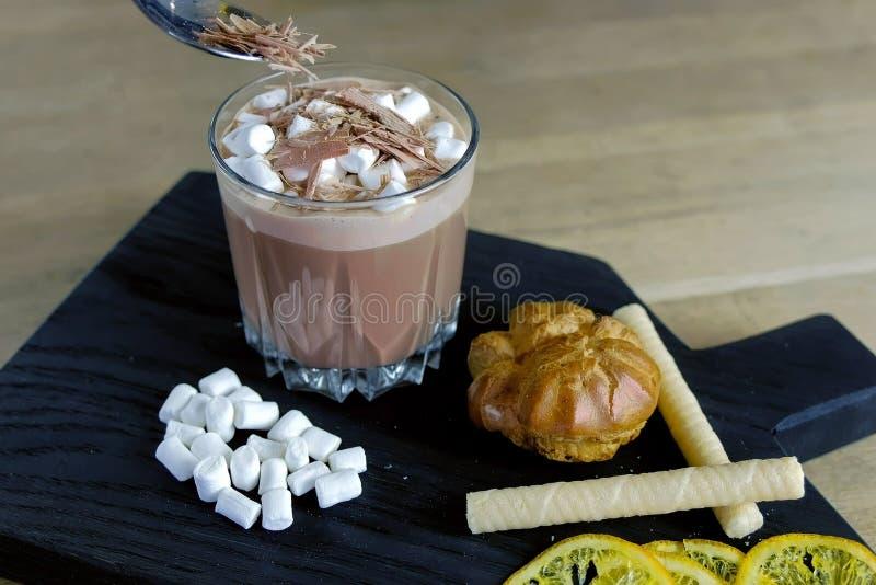 Barista polvilha o chocolate raspado no cacau com o marshmallow no vidro da rocha Cozinhando o cacau Opinião do Close-up fotografia de stock royalty free