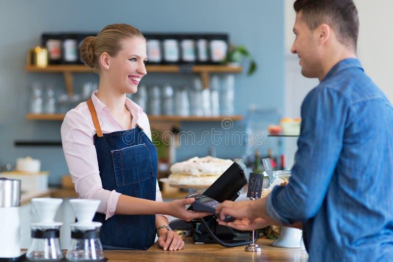 Barista porci klient w sklep z kawą obrazy stock