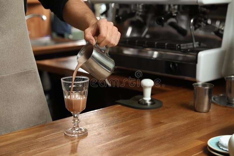 Barista pouring coffee into glass at bar counter, closeup royalty free stock image
