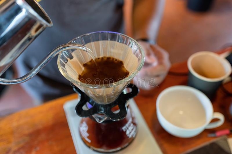 Barista pouring hot water in paper filter with grind coffee royalty free stock photography
