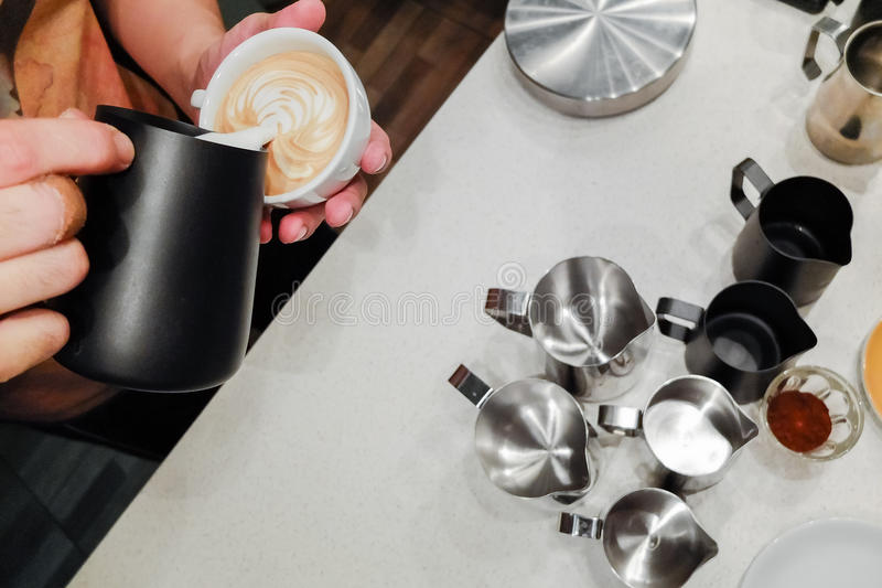 Barista pouring latte art over his pitchers royalty free stock images