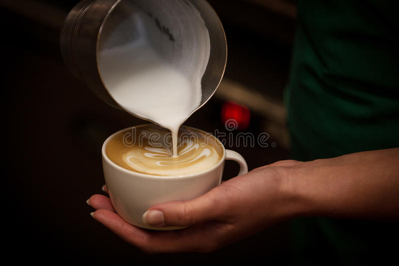 Barista pouring milk in a coffee cup stock image