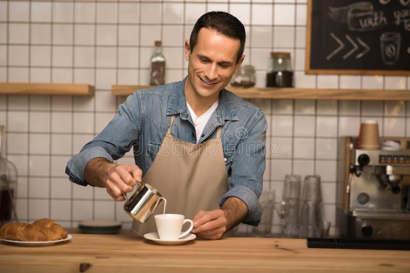 Barista pouring milk into coffee. Portrait of smiling barista pouring milk into coffee royalty free stock photography