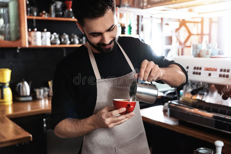 Barista pouring milk into cup of coffee royalty free stock photos