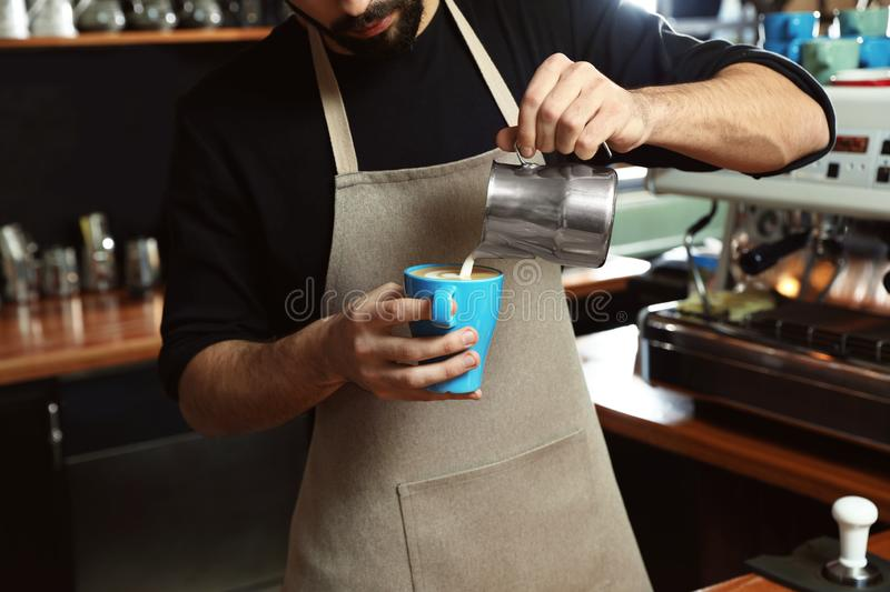Barista pouring milk into cup of coffee in shop stock images
